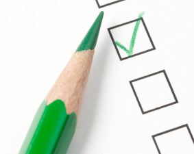 Green check box on survey box with green pencil. Focus on tip of pencil